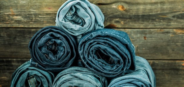 木製の壁にねじれたジーンズの束、ファッショナブルな服