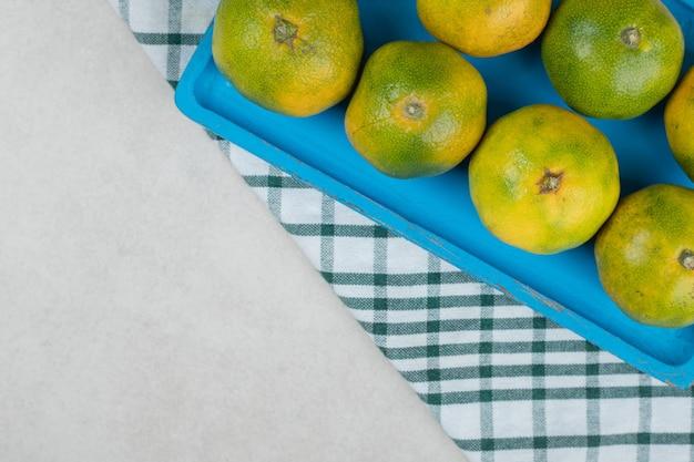 Букет сочных мандаринов на синей тарелке