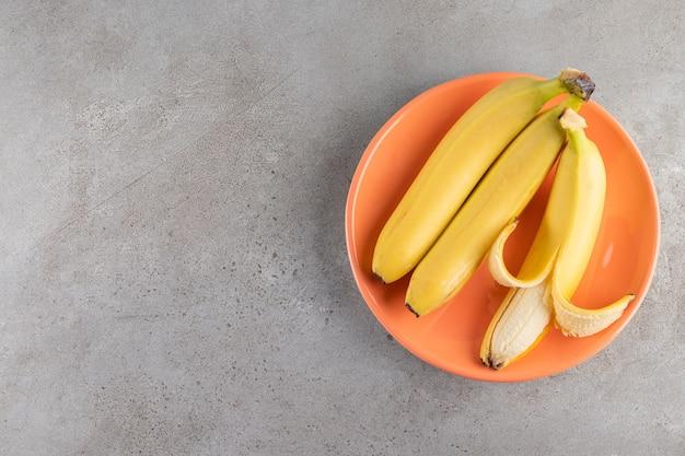 Гроздь сочных желтых бананов на каменной поверхности