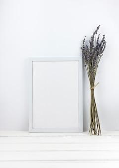 木製の机の上の空のフレームとラベンダーの花の束