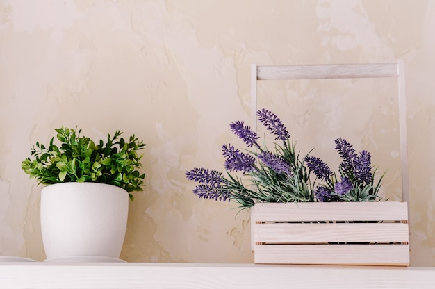 Букет из лаванды в деревянной коробке и зелени в вазе на белом столе на винтажной полке над пастельной стеной. шикарный декор в стиле прованс для фермерского дома. украшение дома в стиле прованс.