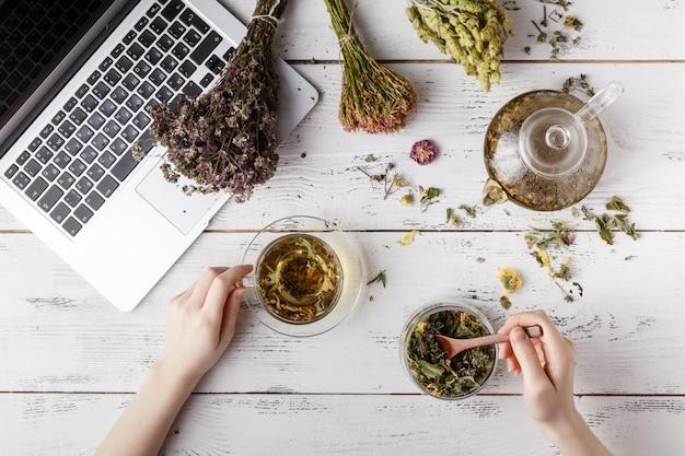 Куча лекарственных трав, чашка здорового чая и мешок сухих здоровых coneflowers на деревянной доске. фитотерапия.