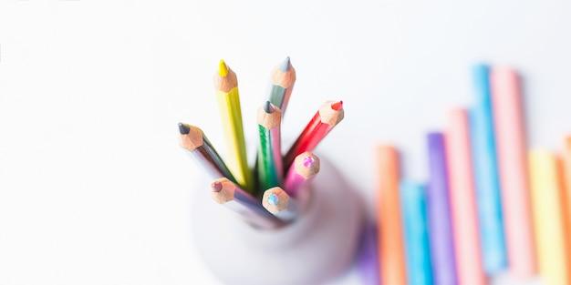Букет из разноцветных карандашей в чашку мелки. вид сверху на белом фоне.