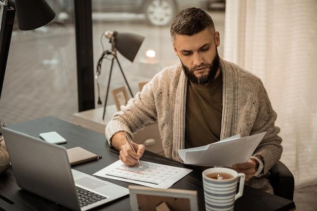 Пачка бумаг. смущенный самозанятый бородатый мужчина листает бумаги, составляя график на следующий месяц