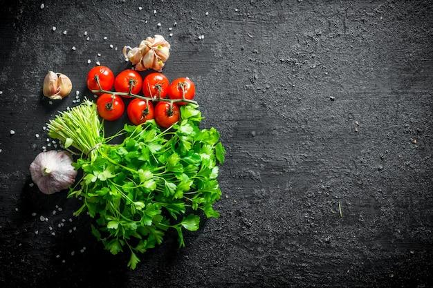 Пучок петрушки с помидорами черри и зубчиками чеснока на черном деревянном столе