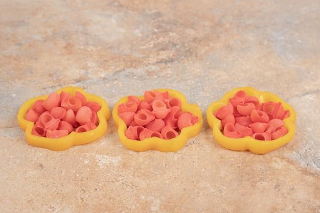 オレンジ色の背景にピーマンスライスのパスタの束