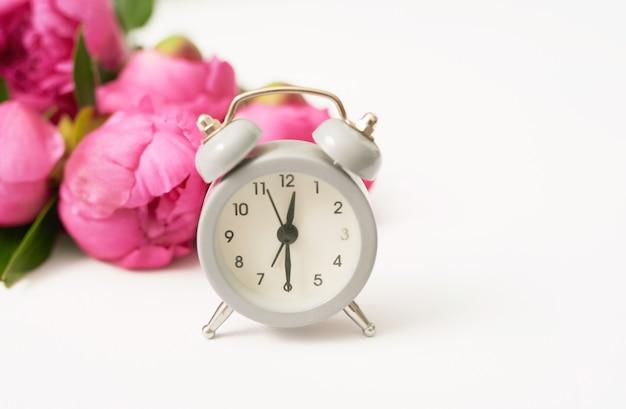 牡丹の花と目覚まし時計の束