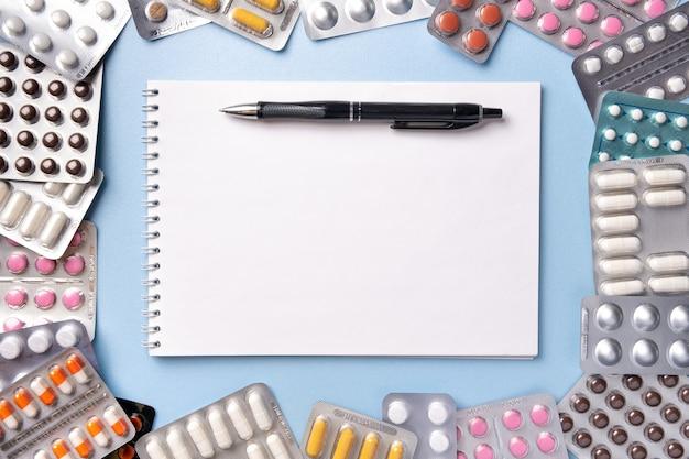 노트북 및 펜, 복사 공간 파란색 배경에 물집 팩에 다른 색상의 알 약의 무리. 의약품 제조법에 대한 처방전 공란.