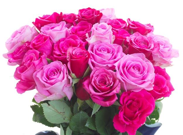 白い背景で隔離のピンクとマゼンタの新鮮なバラの束