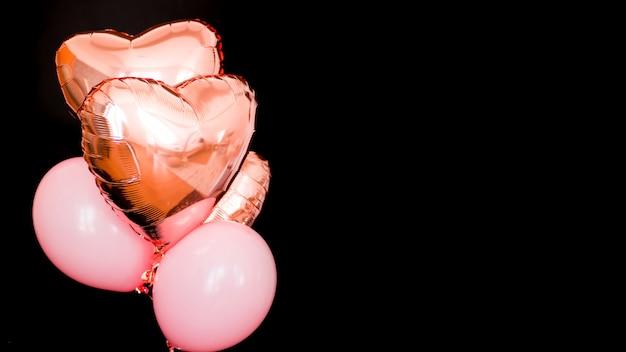 黒の背景に分離されたピンク色のハート型のホイル風船の束。愛。休日のお祝い。バレンタインデーのパーティー。誕生日パーティー、結婚式、お祭りの装飾の要素。