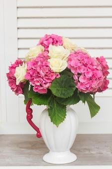 花瓶に白いバラとピンクのオルテンシアの花の束