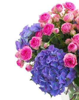 ピンクのバラと青いアジサイの花の束が白いスペースに孤立してクローズアップ