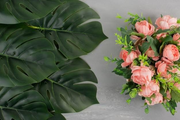 회색 표면에 잎 핑크 장미 다발