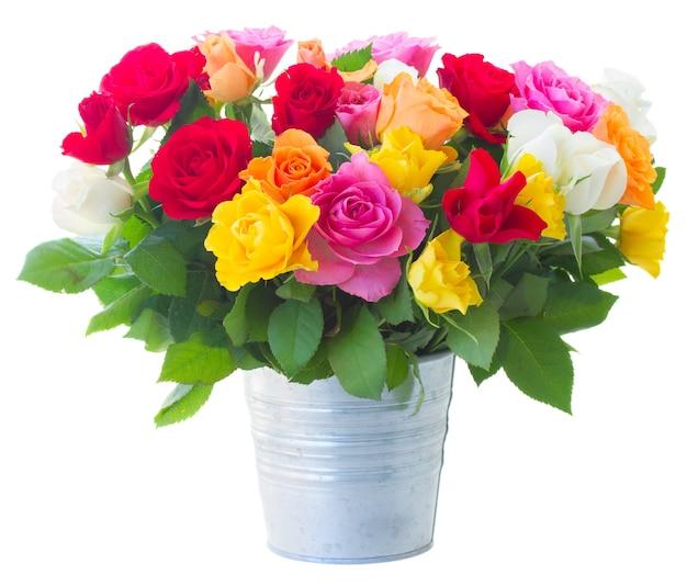 白で隔離の金属製の鍋にピンク、黄色、オレンジ、赤、白のバラの束