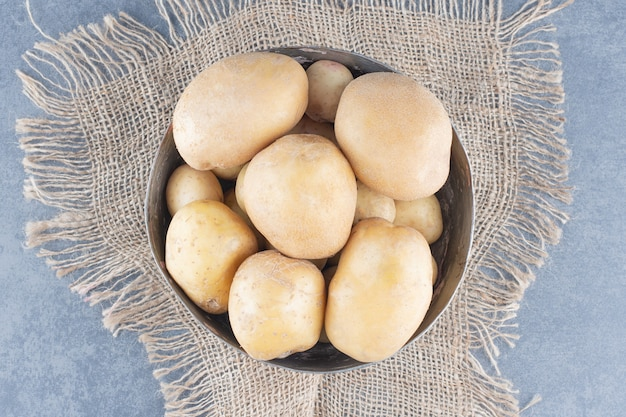 黄麻布と金属マグカップのジャガイモの束。