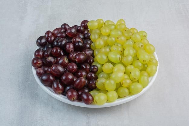 하얀 접시에 보라색과 녹색 포도의 무리. 고품질 사진
