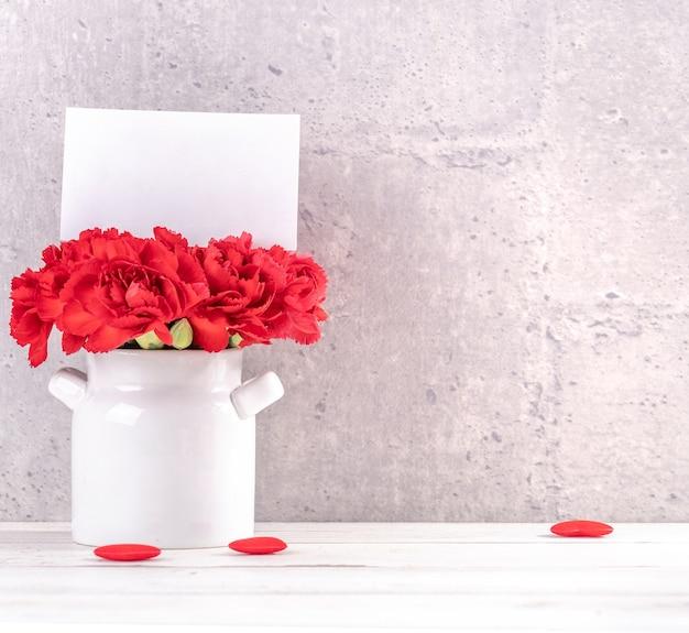 어머니의 날 인사말 개념 꽃병에 빨간 카네이션의 무리.