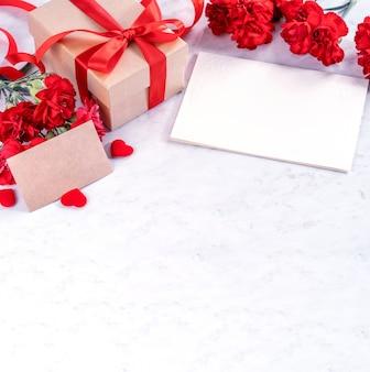 어머니의 날 인사말 개념에 대 한 선물 상자와 붉은 카네이션의 무리.