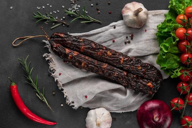 Пучок красной сухой домашней колбасы на темной поверхности, чеснок и мешковина, вид сверху