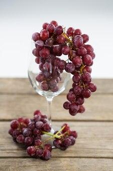 木製のテーブルの上のワイングラスの赤ブドウの束