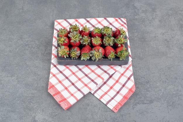검은 접시에 빨간 딸기의 무리입니다. 고품질 사진