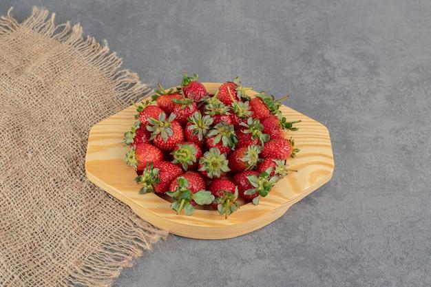 Букет из красной клубники на деревянной тарелке. фото высокого качества