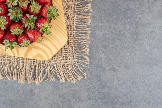 나무 접시에 빨간 딸기의 무리입니다. 고품질 사진