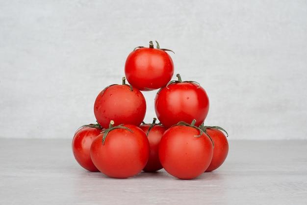 白いテーブルの上の赤いトマトの束。