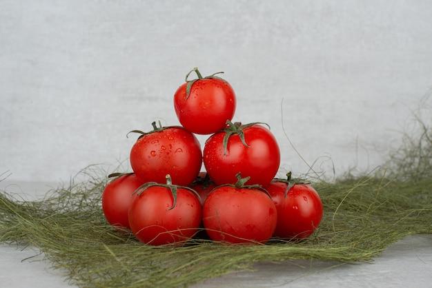 緑の黄麻布と白の赤いトマトの束。