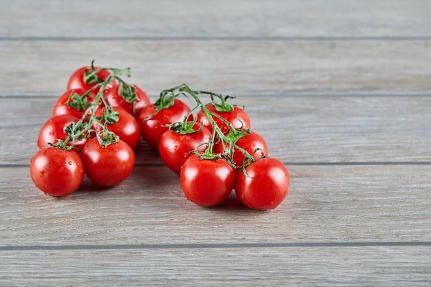 木製のテーブルの上の枝と赤いトマトの束