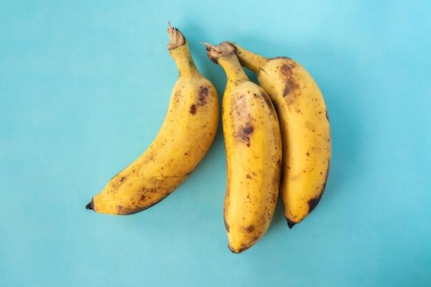 파란색 배경에 익은 바나나의 무리입니다. 평면도. 스톡 사진을 닫습니다.