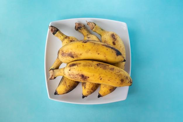 파란색 배경에 흰색 접시에 익은 바나나의 무리. 평면도. 스톡 사진을 닫습니다.