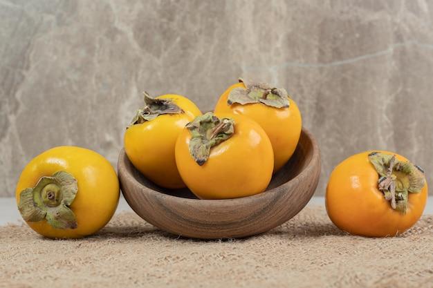 木製のボウルに熟したおいしい柿の束。