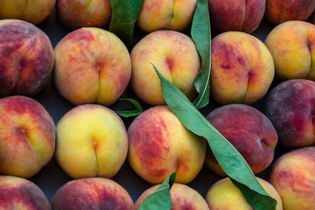 ファーマーズマーケットに山積みになっている熟した新鮮な有機桃の束