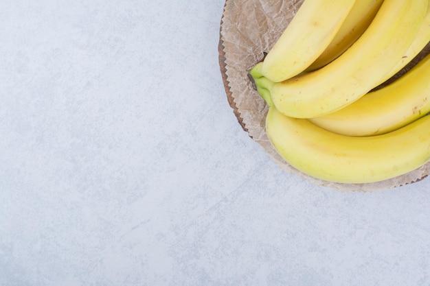 Букет из спелых плодов бананов на деревянной тарелке. фото высокого качества
