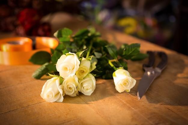 Roseと木製のテーブルにポリリボンとバラの花束