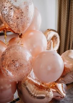 自宅でヘリウムと光沢のあるピンクの風船の束