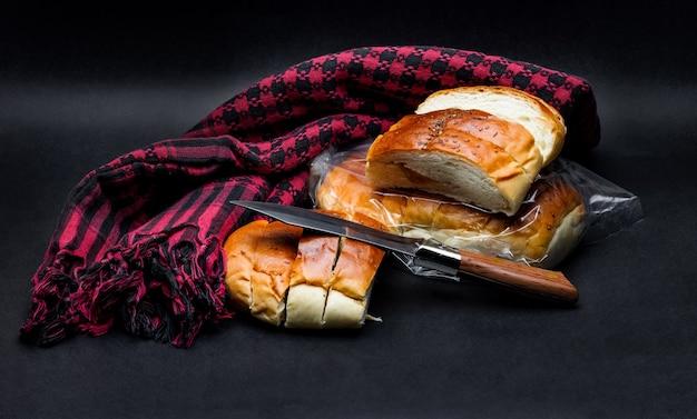 暗い粗い背景にナイフと赤い布でスライスされたパンの束