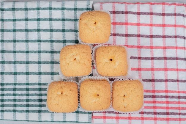 カラフルなテーブルクロスに柔らかいクッキーの束。高品質の写真