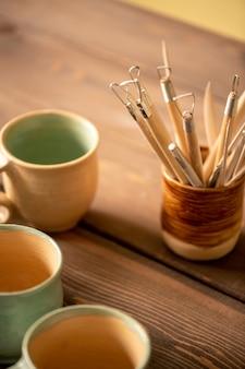 Связка специальных ручных инструментов для работы с глиной и изготовления фаянса на деревянном столе с группой чашек рядом