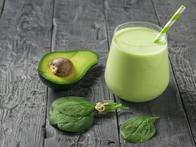 나무 탁자에 있는 시금치 잎, 아보카도, 스무디. 피트니스 제품. 다이어트 스포츠 영양.