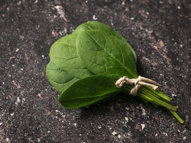 시금치의 무리는 돌 배경에 나뭇잎. 건강을 위한 음식. 채식주의 자 음식. 정상에서 본 모습.