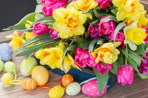 봄 핑크 튤립과 부활절 달걀과 노란 수선화 꽃의 무리