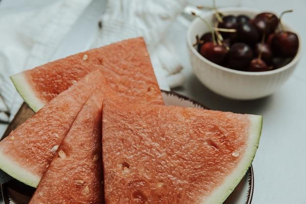Букет лета и свежих фруктов за минималистским белым столом, арбуз и вишня, концепции оздоровления и здорового питания, вкусные, текстурированные, копировальное пространство