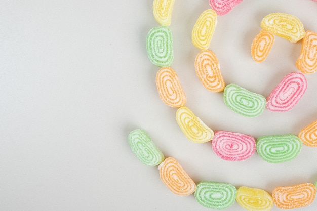 베이지 색 표면에 달콤한 젤리 사탕의 무리