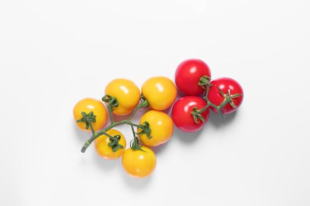 黄色と赤のデザインのための白い背景の上のトマトの束