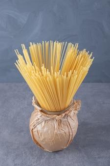 花瓶に生のドライスパゲッティの束。