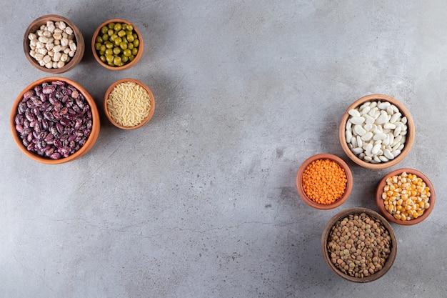 石の背景に未調理のレンズ豆、豆、米の束。