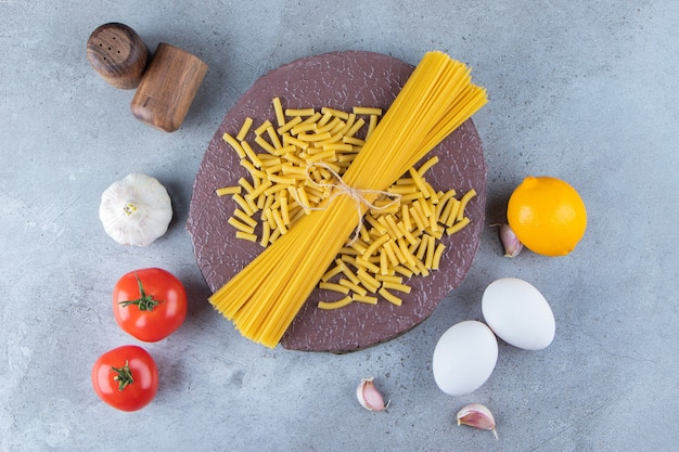 Пучок сырых спагетти в веревке со свежими красными помидорами и чесноком.