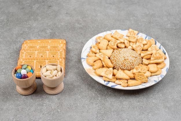 大理石の表面にさまざまなおいしいビスケットやキャンディーの束